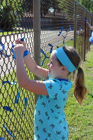 Student tying blue ribbons to chain link fence