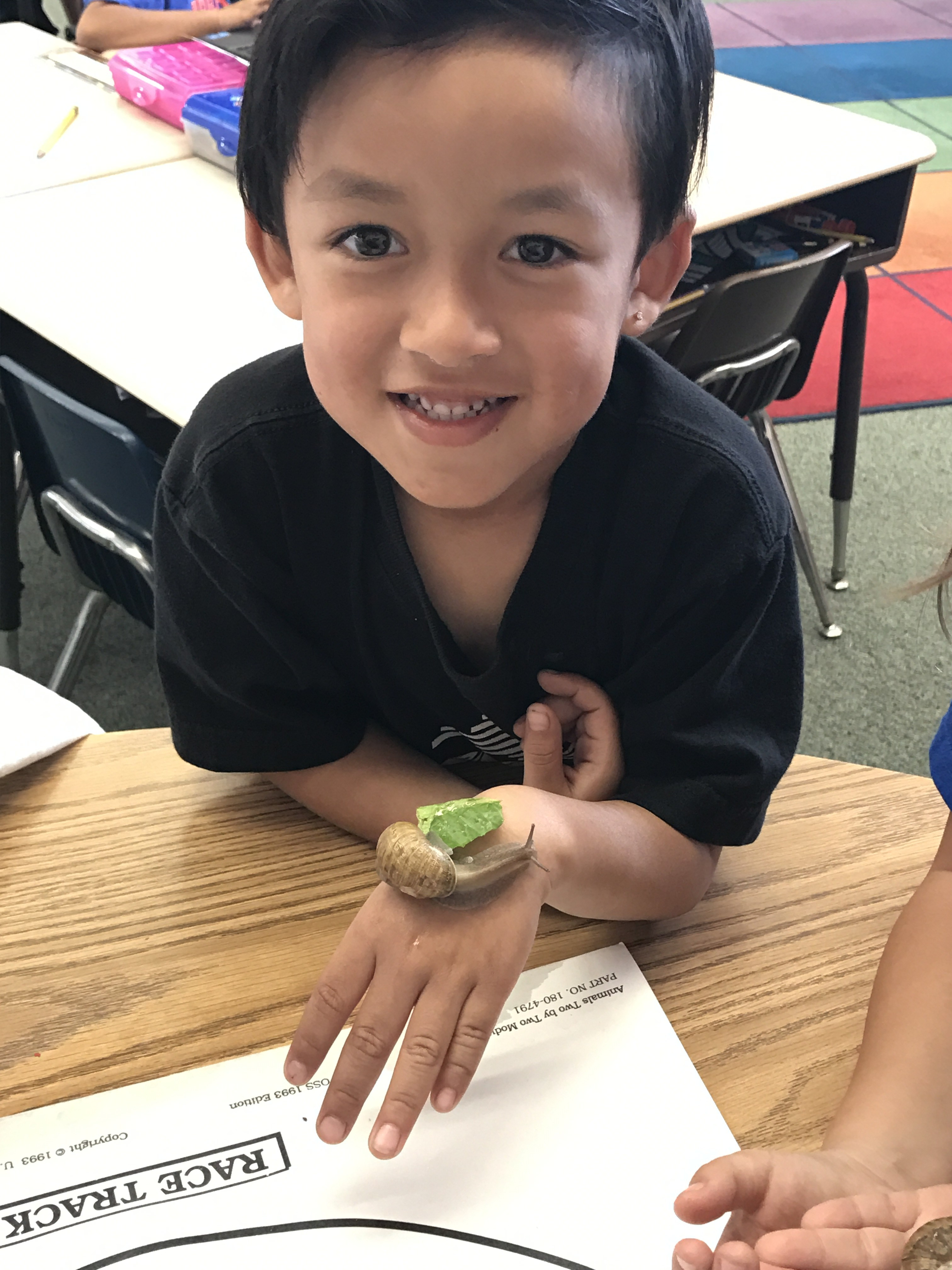 Student exploring feeding a snail on his hand