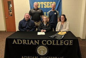 Jaidin Clemens signs her letter of intent to wrestle at Adrian with her coaches and parents.