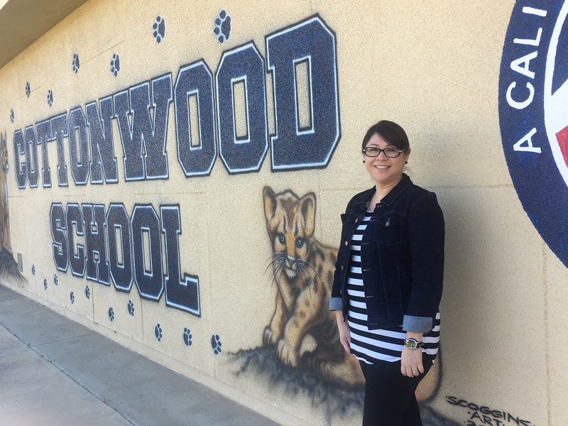 Esmeralda Chavez standing in front of a Cottonwood School sign.
