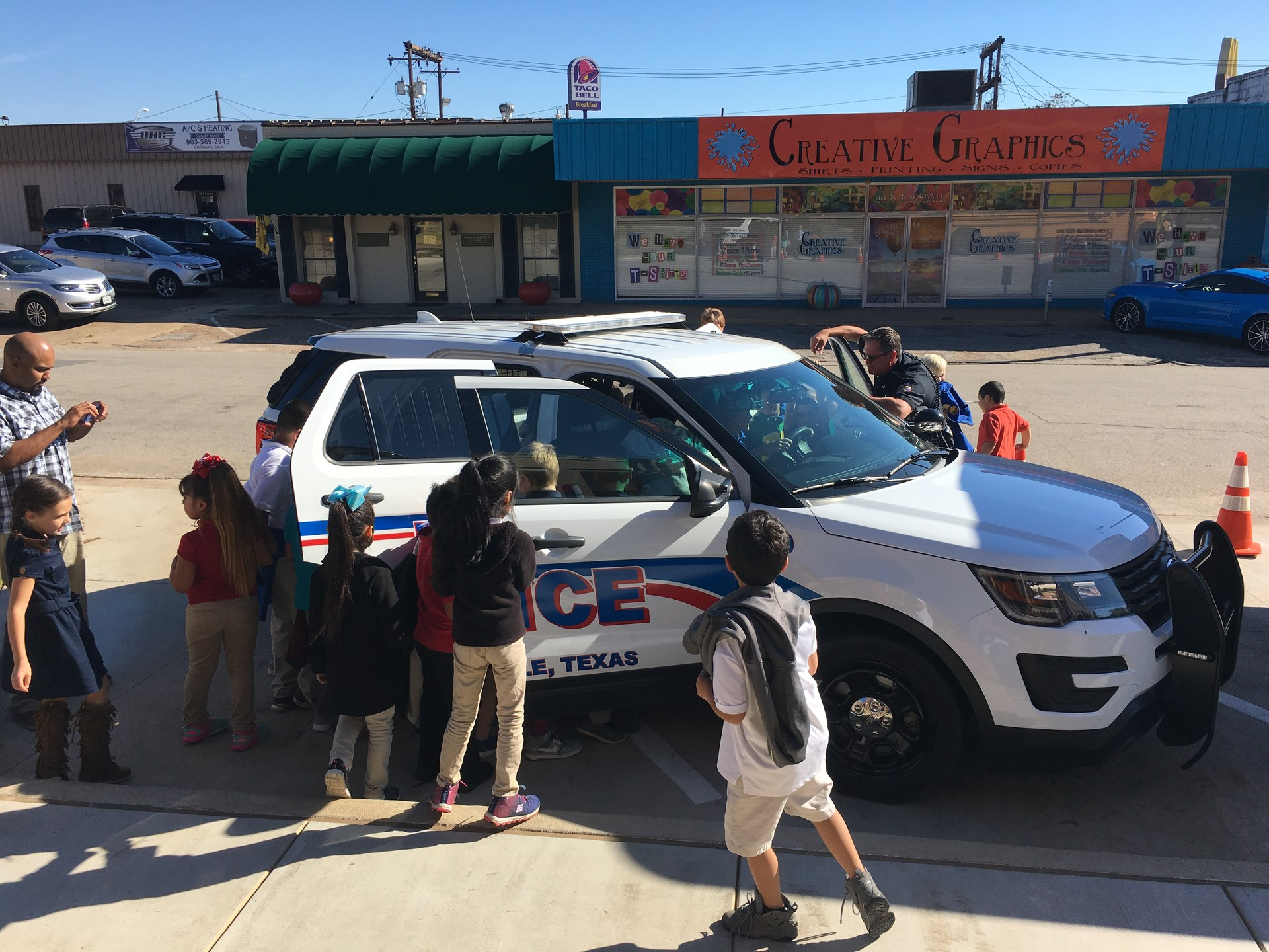 students looking at a police car