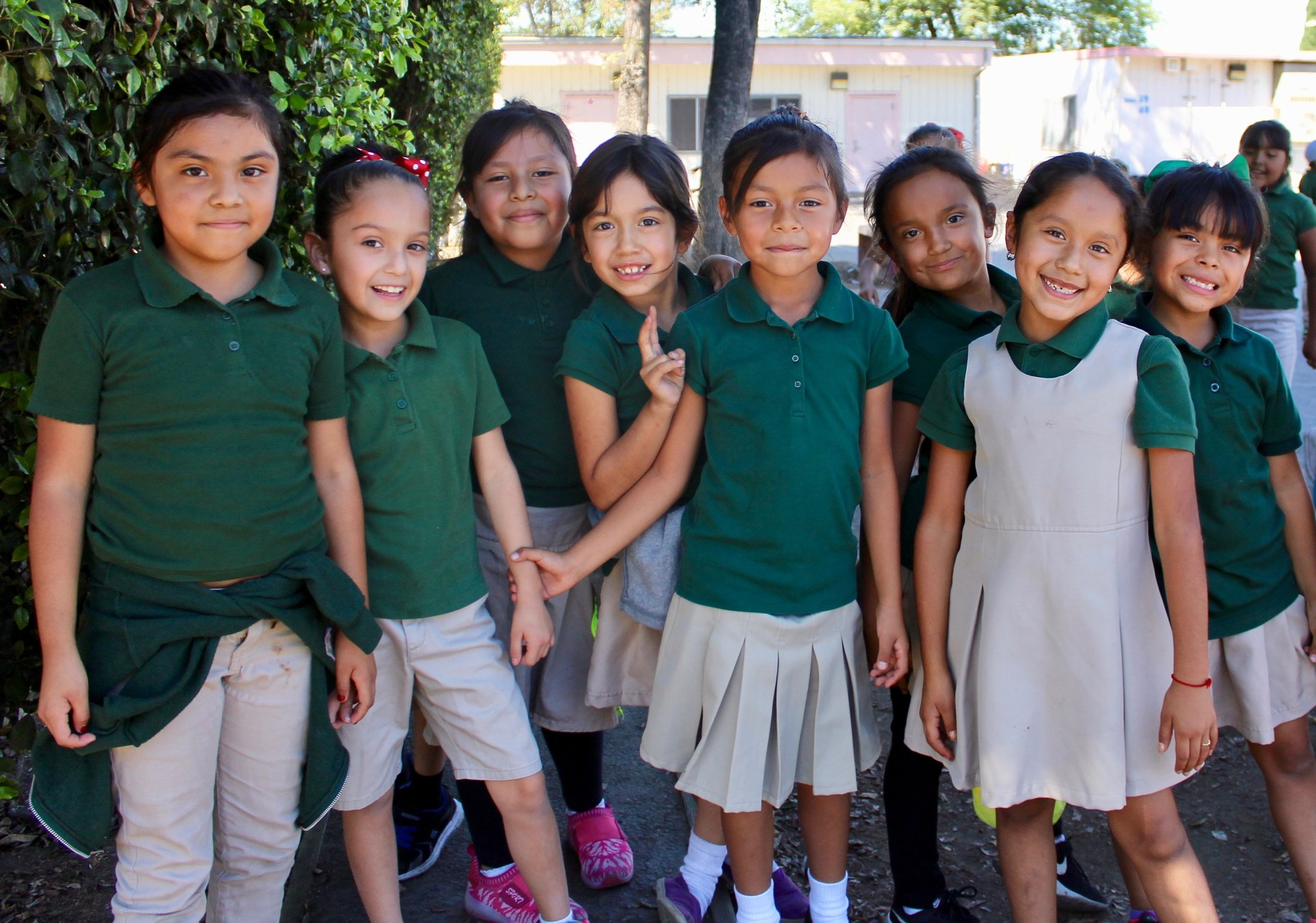 a group of smiling girls in school uniforms