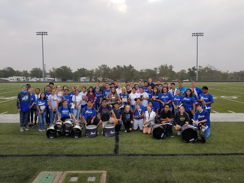 Group of band students on football field posing with their instruments