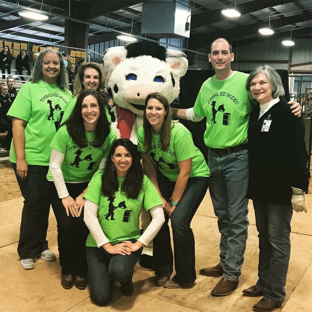 Student Support Staff in green shirts posing with Ms. Moo, a cow character at the TISD Special Rodeo
