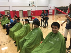 Soto students are lined up in chairs in the school gym waiting their turn to shave their heads to raise money for childhood cancer research.