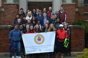 Participants in the 2018 OLSH Love Walk for the Poor pose together on the school steps.