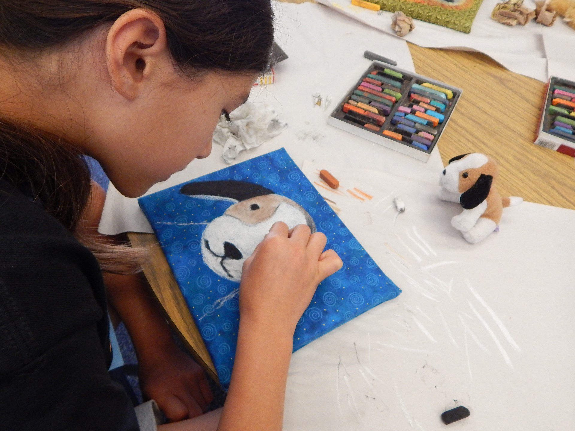 Girl using oil pastels to draw a dog.