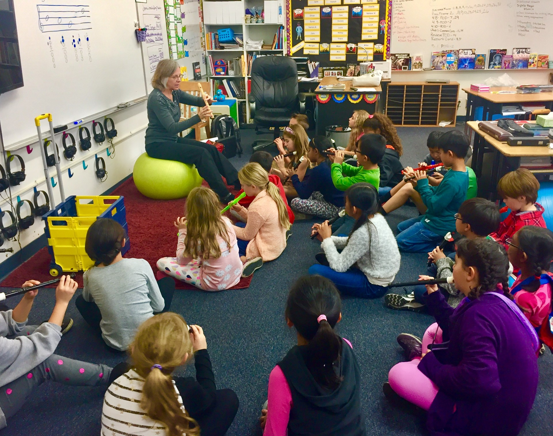 Teacher teaching recorders to a class of students.