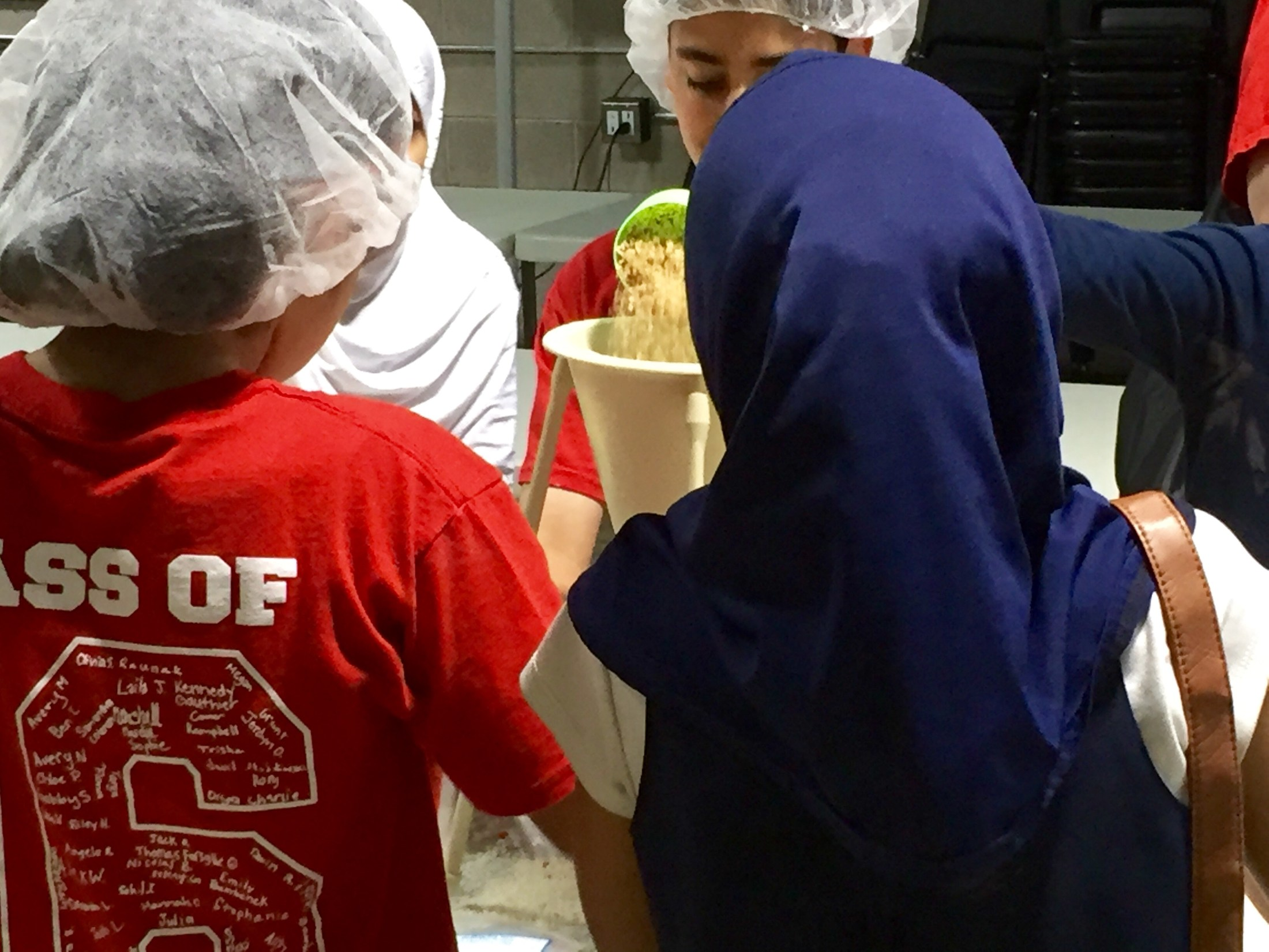 Kids measuring the food at a Kids Coalition Against Hunger packing event.