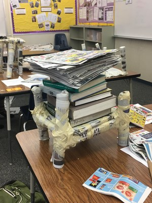 A newspaper table that is holding a variety of heavy books.