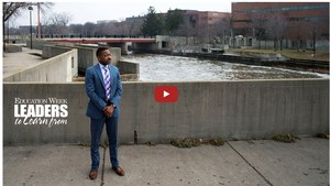 Flint Community Schools Superintendent, Mr. Tawwab, standing downtown Flint in front of the Flint River.