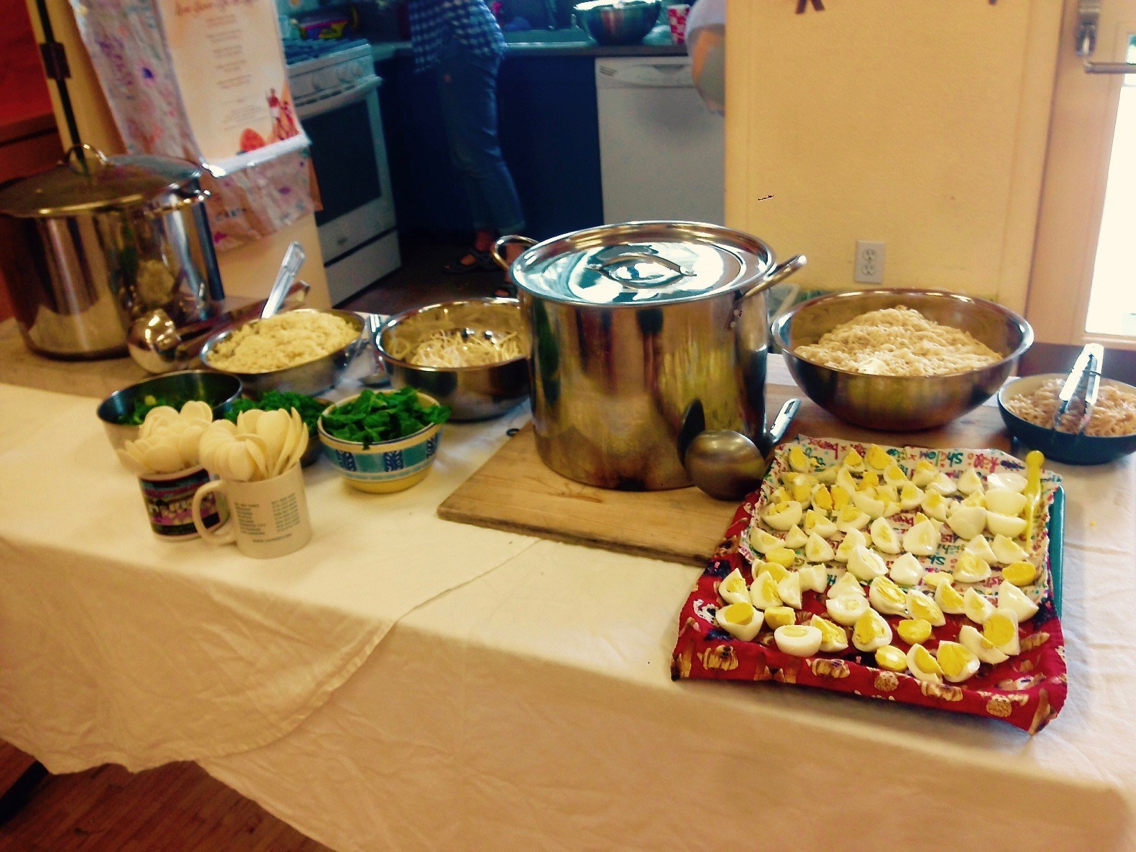 A counter with a large metal pot, ingredients, and cups of spoons