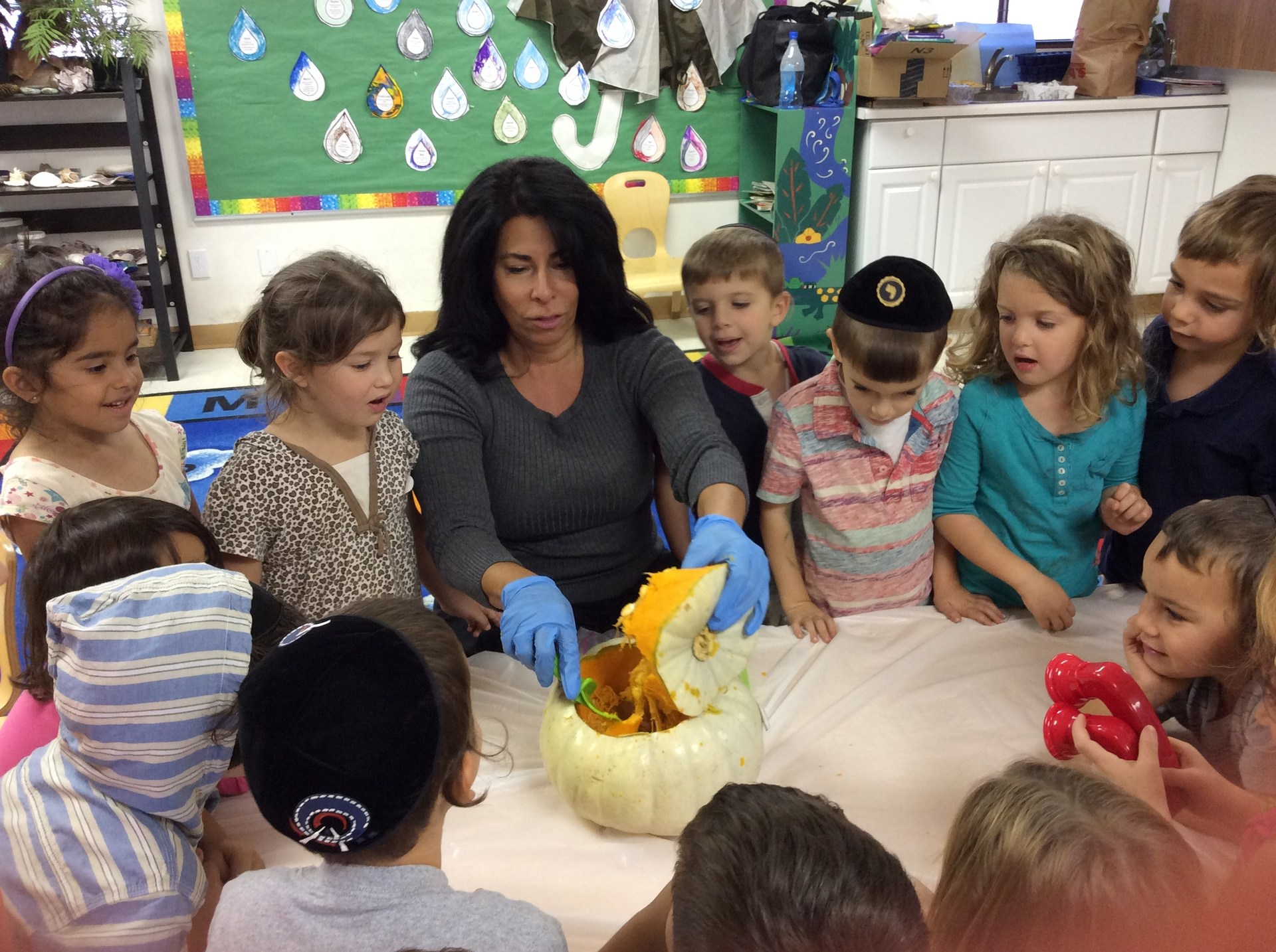 teacher carving a pumpkin with kids watching