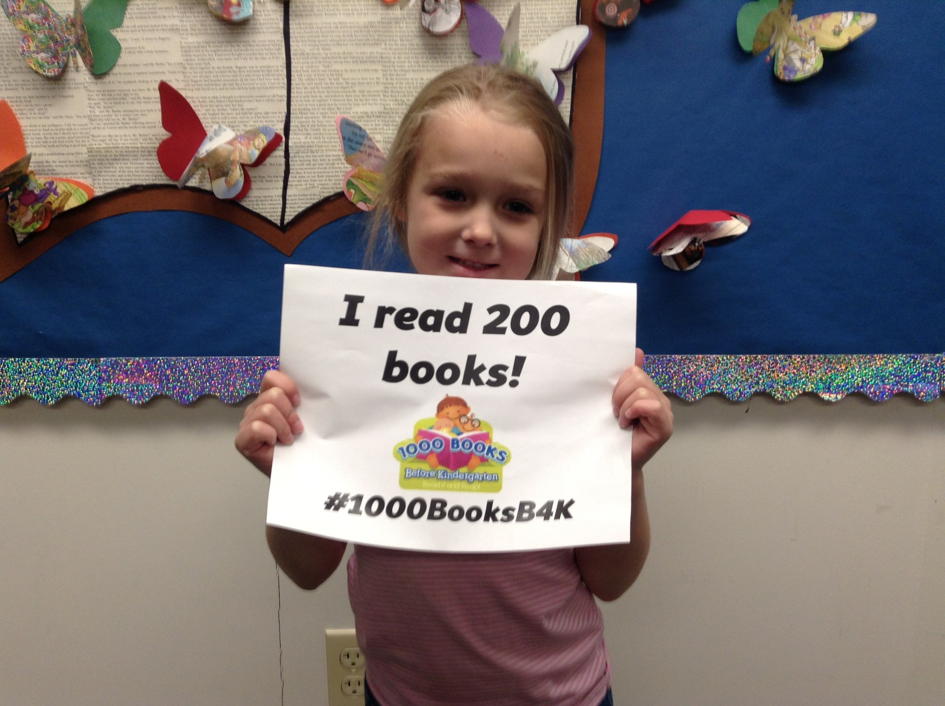 Photo of a preschool student showing that she has read 200 books.
