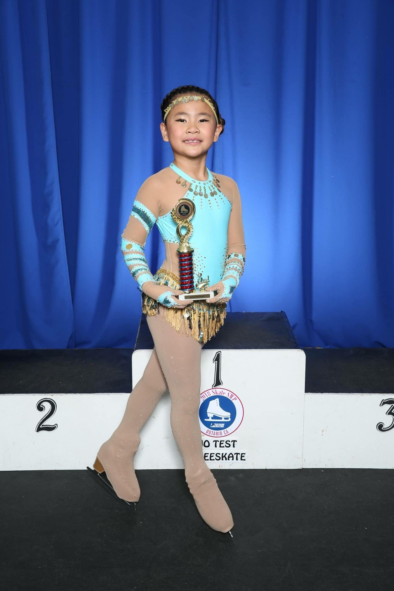 Student with ice skating awards