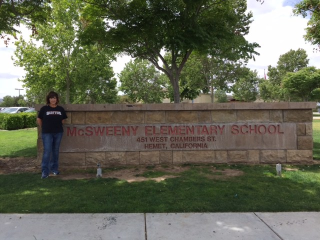 Tanya Barnett in front of a McSweeny Elementary sign.