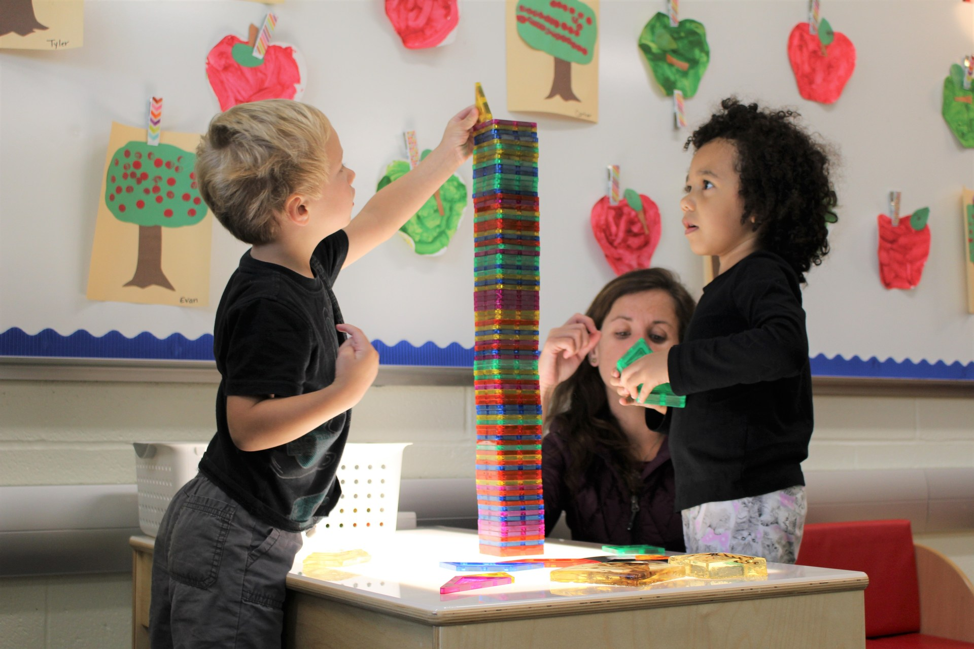 boy and girl in preschool stack blocks on lighted table