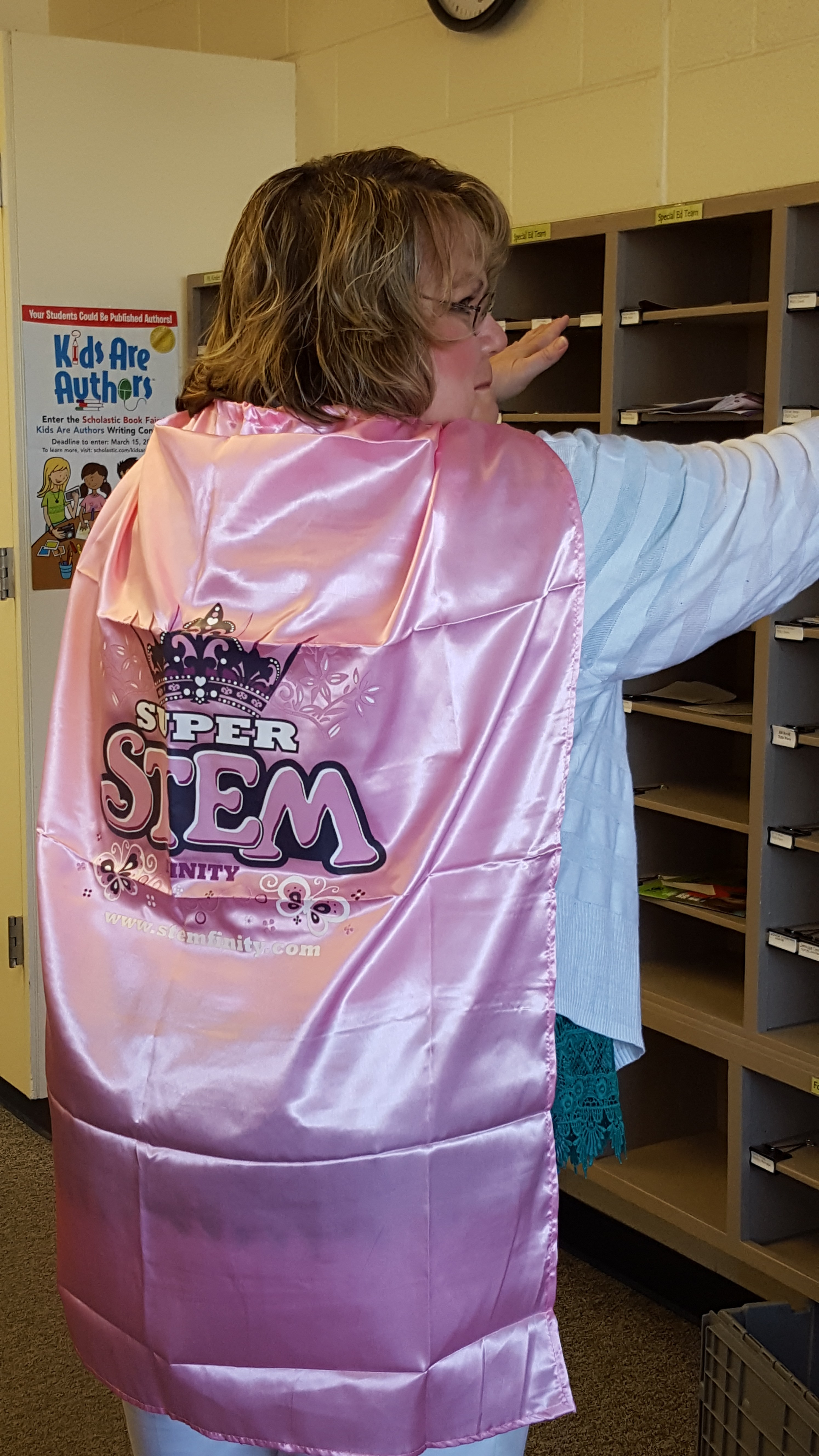 Teacher wearing a cape with 'super STEM' spelled out.
