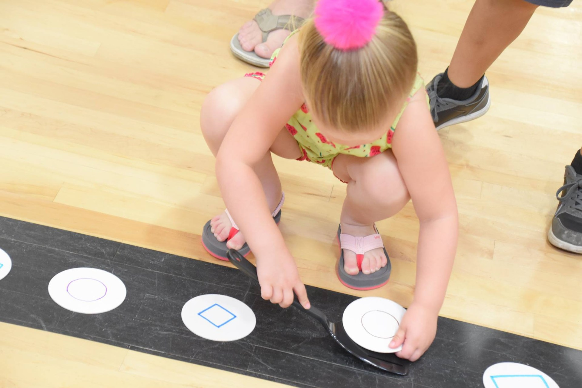 Preschool girl playing the pancake shape relay game.
