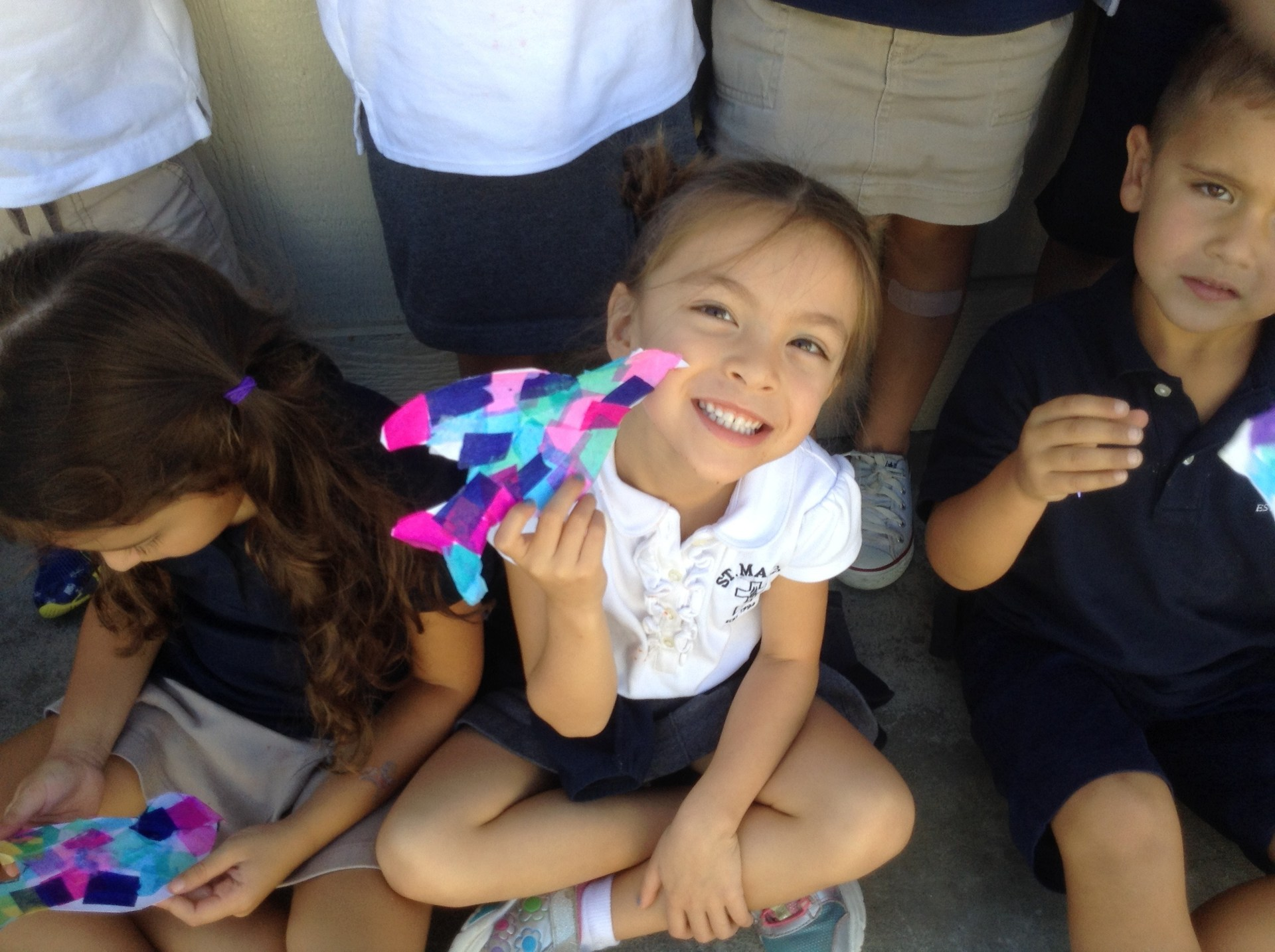 Preschool student holding up a Peace Crane