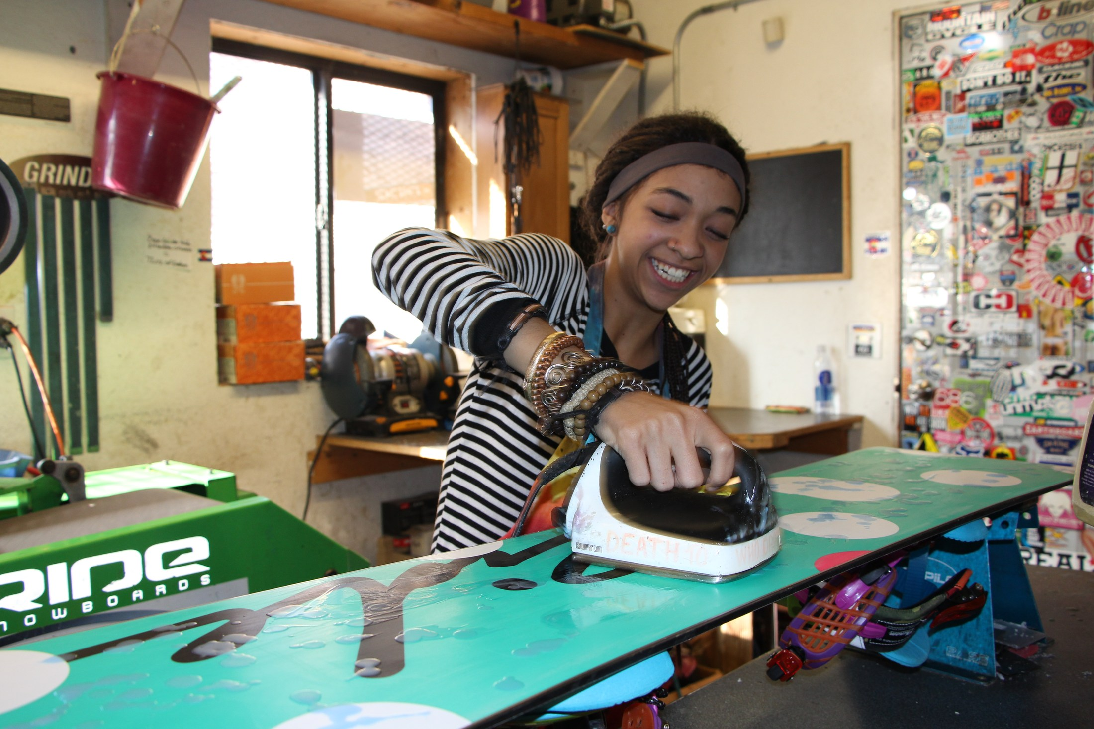 Student waxing a snowboard while interning at a ski shop.