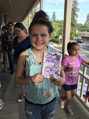 a student with their artwork at the gate art show