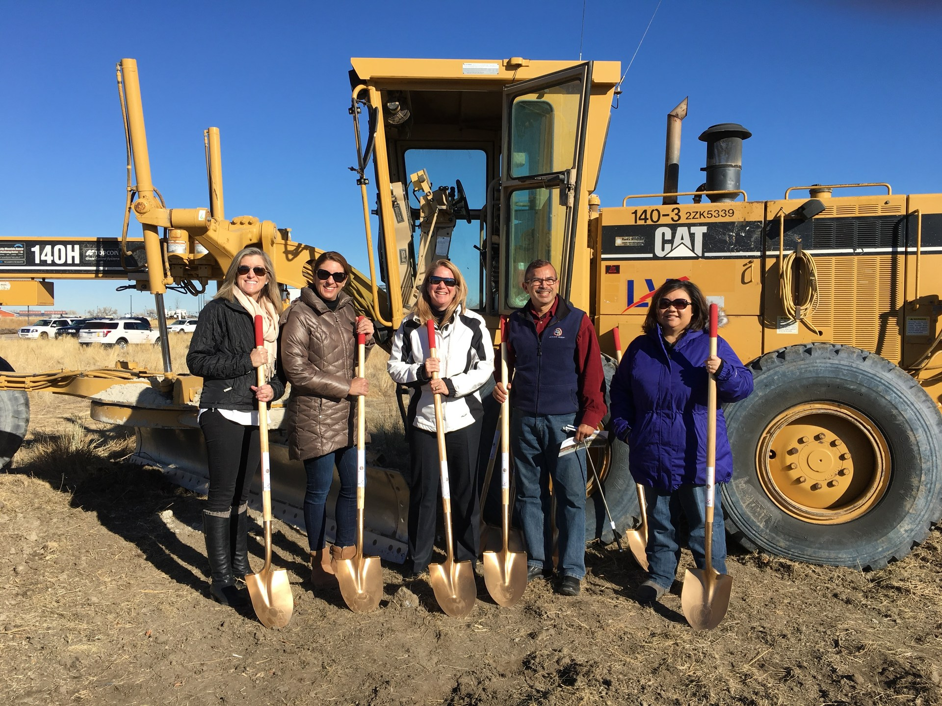 The Board of Directors stands smiling in front of a yellow construction vehicle holding shovels