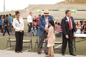 Governing Board President Vic Scavarda shaking hands with a student.