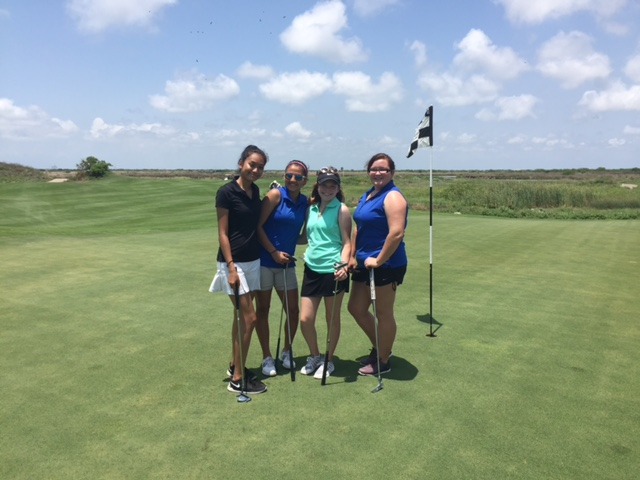 golf girls posing at a hole