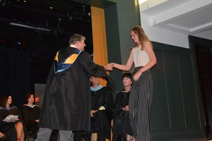 A teacher gives a student an academic award at the honors convocation