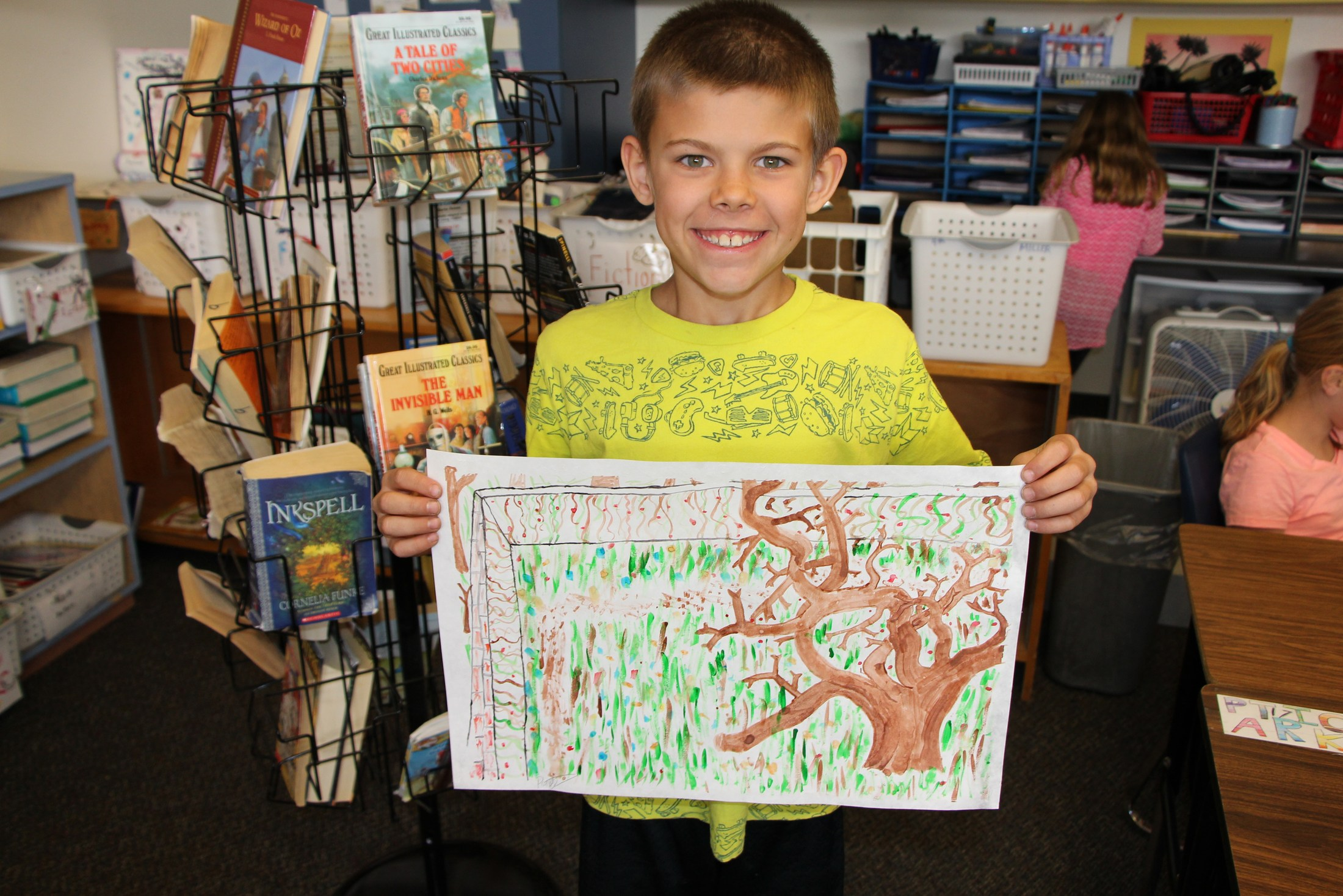 A student holds up a watercolor he created.