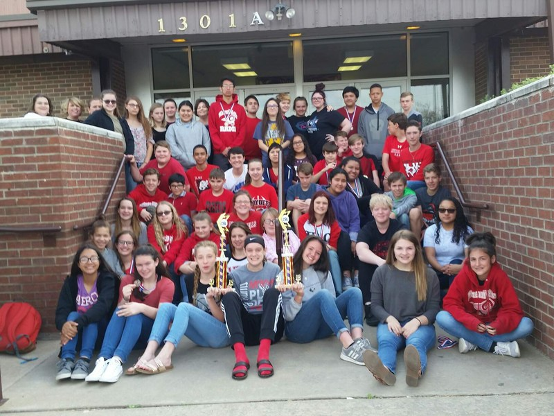 Students seating on steps posing for picture with trophies.