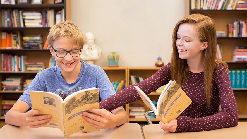 A middle school students points at a line in another middle school student's book