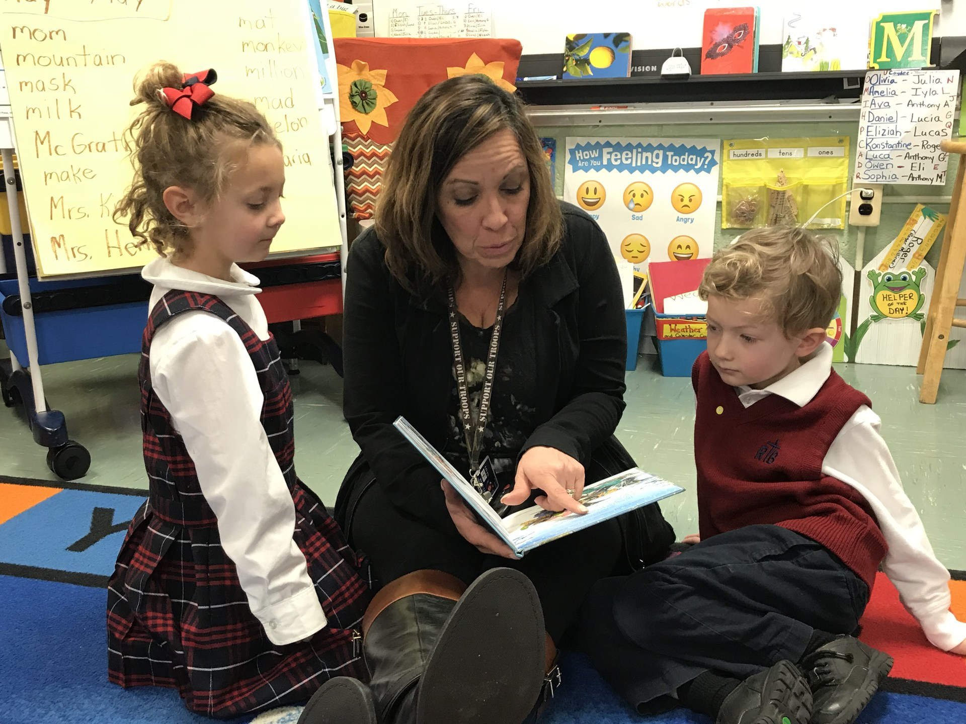 Two students read with teacher