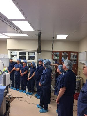 students in scrubs standing observing in a surgery room