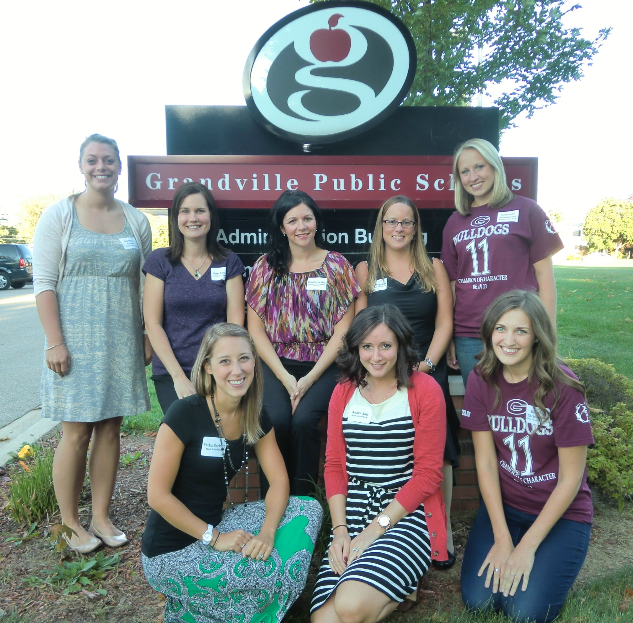 new teachers posing by sign