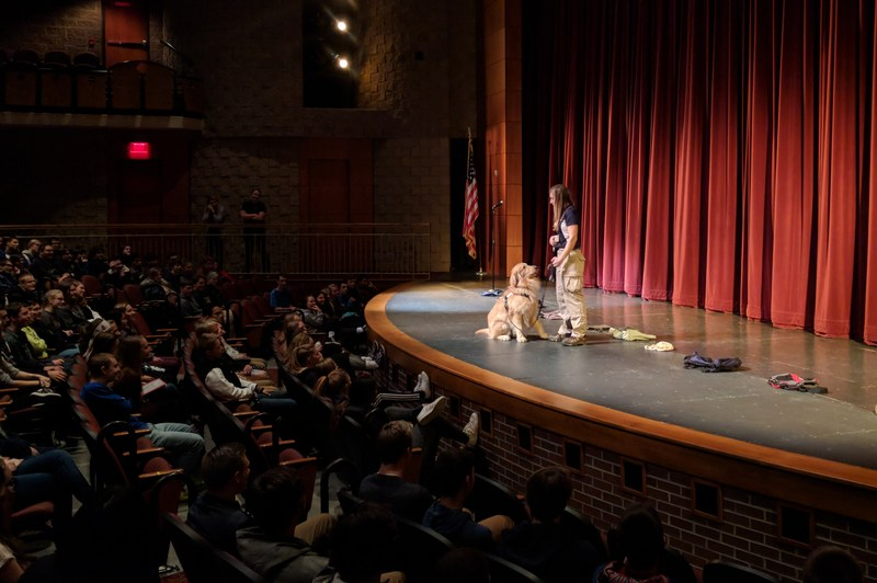 Zeus sits at alert after checking backpacks and purses on stage during the assembly.