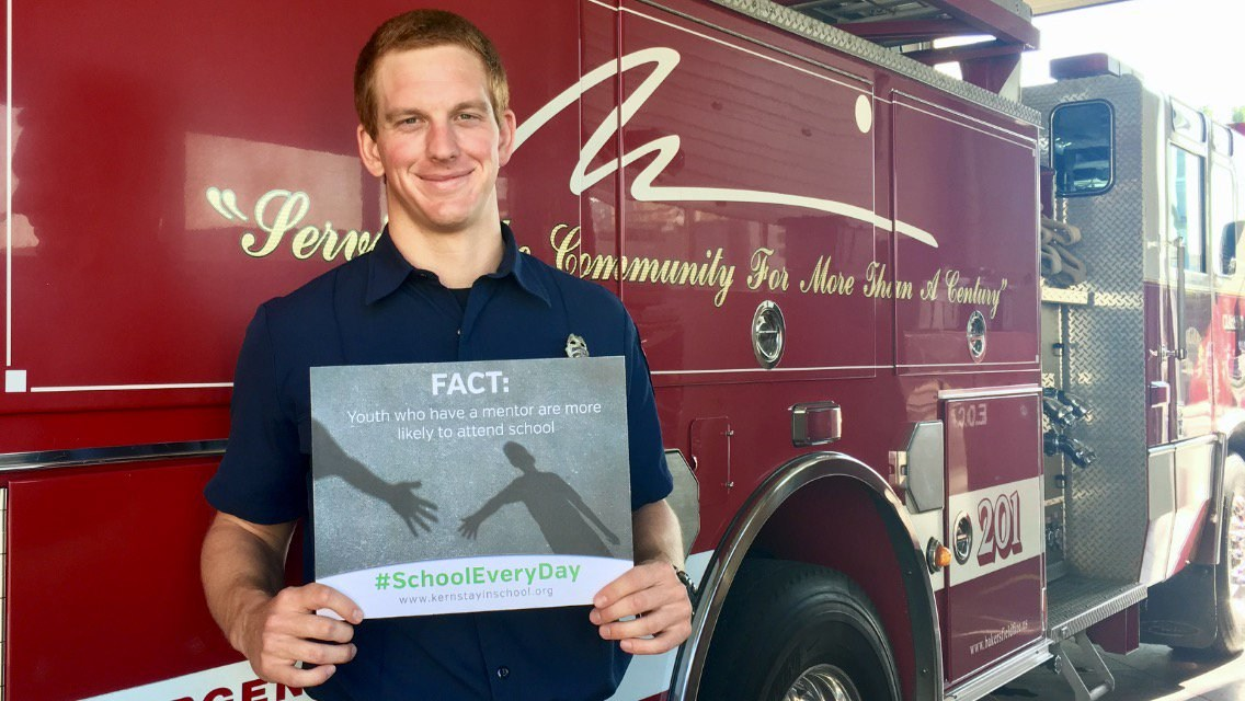 Fireman holding a chronic absence sign