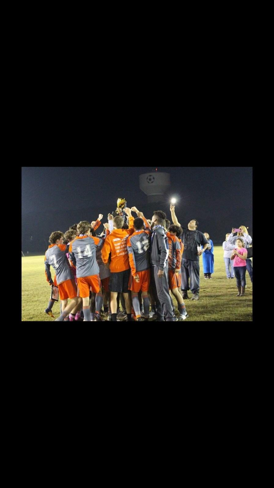 Boys Soccer Team members in a huddle.