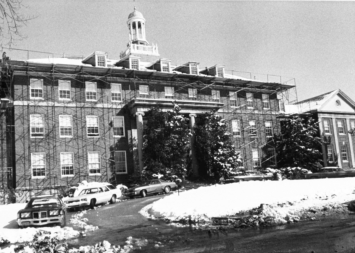Snowy view of Schermerhorn Hall with orginal steps and 2 large pine trees on each side.