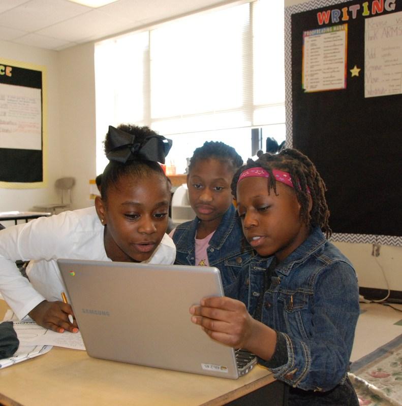 Old North girls gathered around a Chromebook.