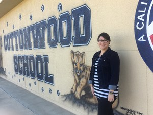 Esmeralda Chavez standing in front of a Cottonwood School sign.