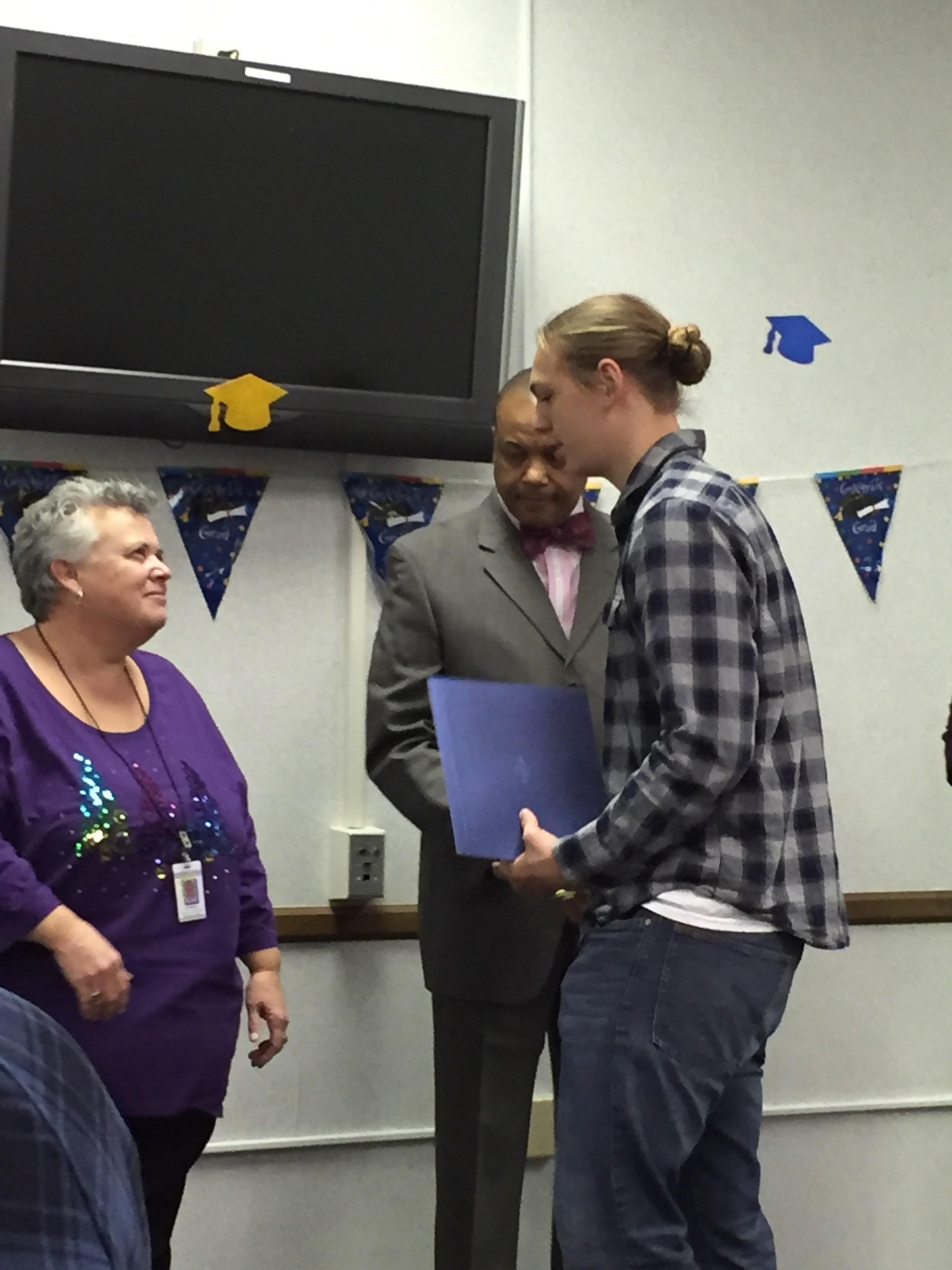 Graduate shaking Mrs. DeAnda and Mr. Jordan hand
