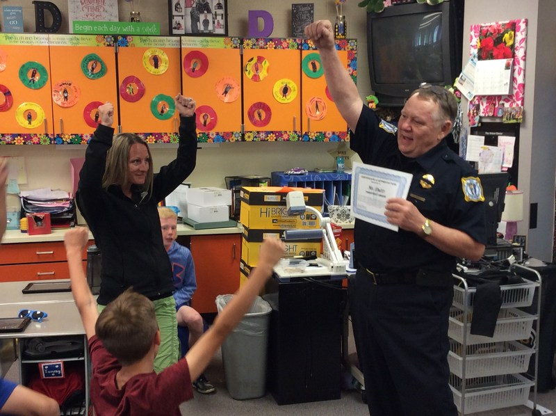 Police officer presenting award to teacher