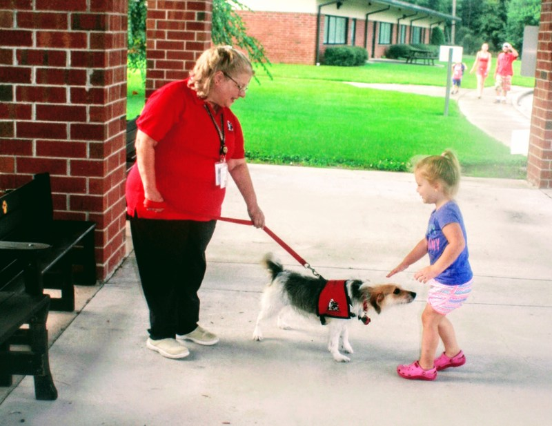 reading dog and handler greeting girl in front of PCPS