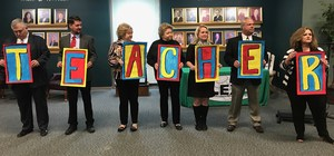 Board of Trustees members read messages from students about great teachers, on the backs of the letters spelling TEACHER.