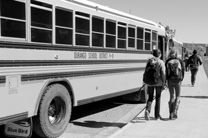 Students line up to get on school bus.