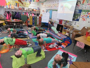 McFall kindergarten teacher Jasmine Koster leads her students in a classroom yoga session.