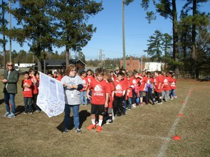 A group of students with red t-shirts out on a field.