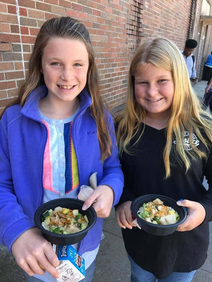 Two female students showing off their healthy and delicious lunch at Dawkins Middle School